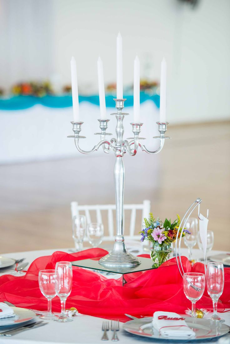 Monte Vista Venue rainbow centerpiece with a white candles on a silver candelabra and a small glass bowl with a mix of flowers in, all on a mirror box surrounded by red organza and a table number hanging from a steel and glass stand.