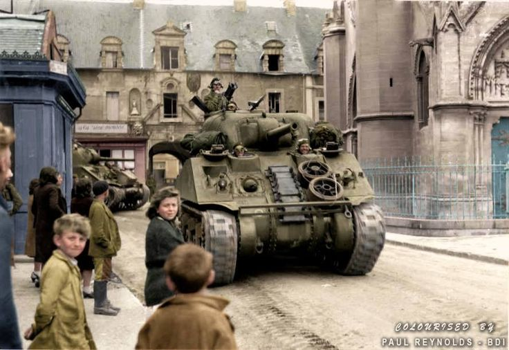 Allied M4 Sherman Tanks pass through Douvres-la-Délivrande on the way to Caen, Normandy, France, June 1944. During the Second World War, Douvres-la-Délivrande was the site of an important German air-detection radar installation, part of the strategic Atlantic Wall defences. Completed in the autumn of 1943, the station was split into two zones by the road from Douvres to Bény-sur-Mer; and heavily fortified with bunkers, machine guns and minefields...