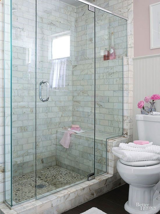 Add a walk-in shower that enhances a small bathroom's usefulness and beauty. This shower stands out in a simply furnished bath, thanks to its distinctively tiled walls and river-rock-tiled floor that are easily seen through a frameless glass shower enclosure. The glass enclosure stair-steps up a marble frame, highlighting the shower bench and a toiletry shelf that aligns with the beaded-board wainscoting's upper trim.:
