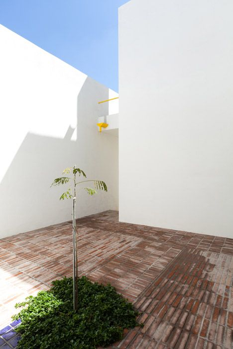 Architect Oscar Gutiérrez used bright yellow paintwork to pick out often-overlooked details on the clean white facade of this courtyard house in Mexico
