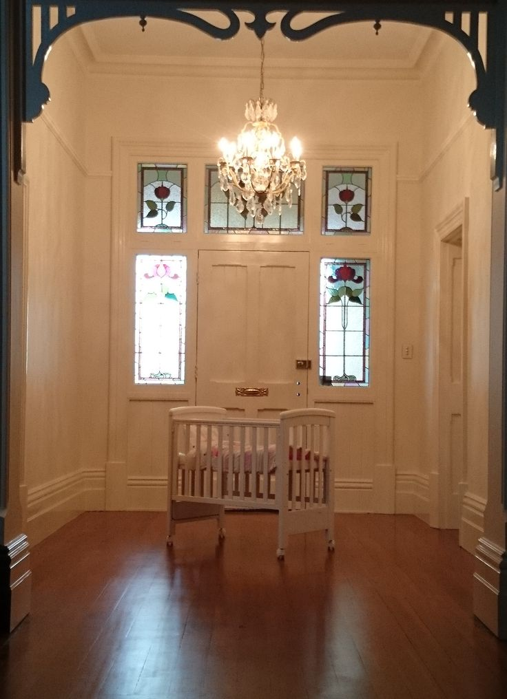 Treppy Dreamy Mini white Bassinet co-sleeper in an entry hall with stained glass lead light and antique chandelier