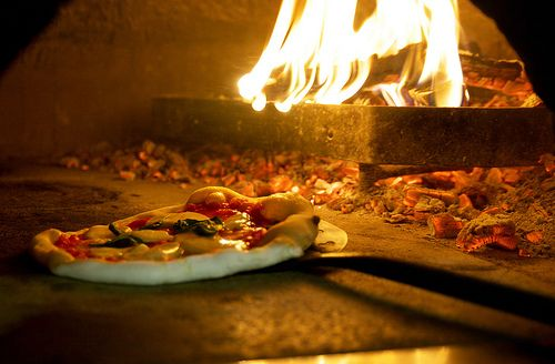 Pizzas being cooked on an open flame, giving the pizzas the taste that keeps you coming back!