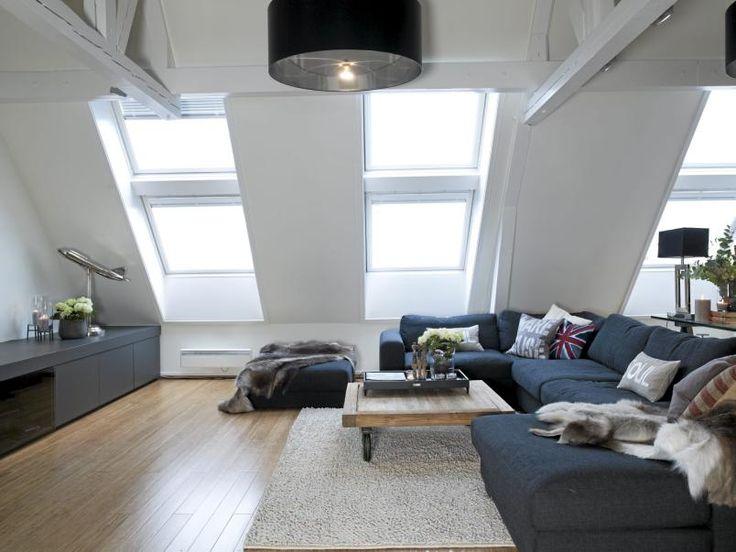 I stuen er loftets takhøyde utnyttet maksimalt med synlige, hvite ...