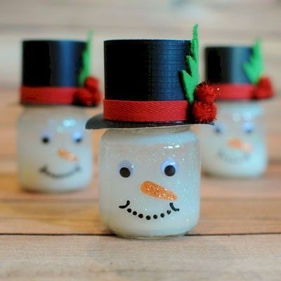 Snowman Snow Globes made from baby food jars. Instructions for these and other winter crafts at FreeKidsCrafts.com