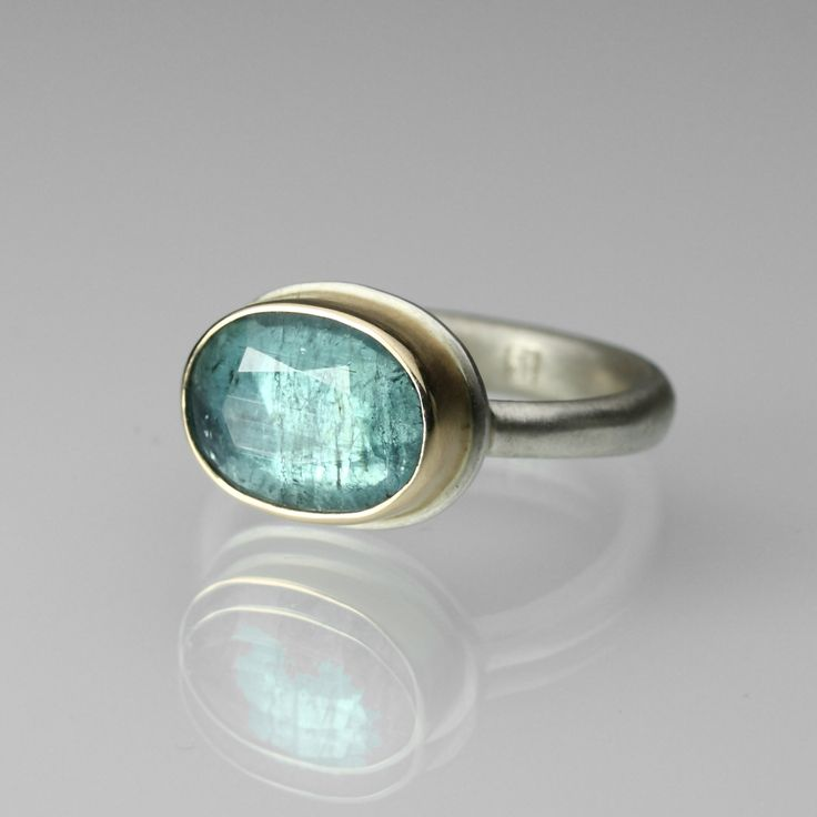 "Blue Tourmaline Ring by  Jamie Joseph  |  Naturally colored blue tourmaline, oval faceted gemstone is set in 14K yellow gold bezel and sterling silver ""Egyptian"" band. Stone measures 9.7mm x 12.8mm, Size 6.75, $1,230.00"