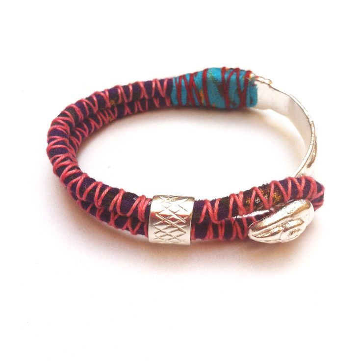 This Firm handmade bracelet is made half of a silver or bronze bracelet, and half of a colored thick rope decorated with colored thread & a small silver ring.
