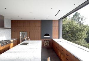 Cucina king size per la villa di Beverly Hills Oak Pass House. I progettisti di Walker Workshop hanno creato due blocchi con piani di lavoro e top in marmo e una serie di mobili custom made in noce. Nicchia strategica per la legna da ardere, vista sugli alberi