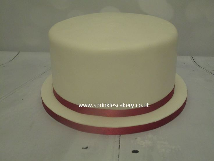 """A simple white iced sponge can be finished with any colour ribbon. Our standard celebration cakes stand at 3.5"""" high."""