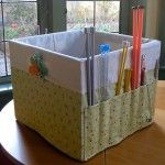 Knit/crochet stoarge...Collapsable bin with fabric scored pouch on side for needles and yarn and patterns in the bin.