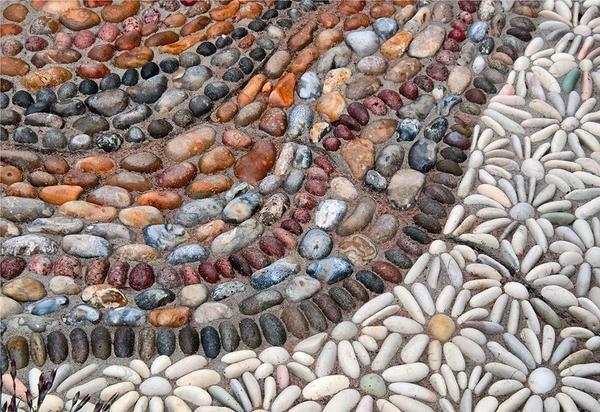 Рядом с каменными белыми цветками струятся ленты красного, коричневого, бежевого, серого и черного гравия. Такой причудливый рисунок придает садовому пейзажу изящество и изысканность.