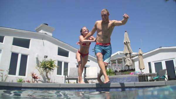 Girlfriend pushing boyfriend into swimming pool Royalty-free stock video