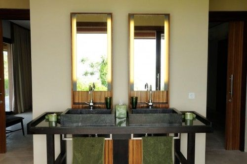 Bulung Daya Holiday Villa Rental. The bathroom has 2 stone sinks set in a piece of furniture created by Warisan, the acclaimed #Bali high end designer, a shower with a view on the sea, walk-in clothes cabinets, and a separate toilet area. The bathroom boasts a splendid view on the nearby cliff. #Luxury #Vacaton #Travel