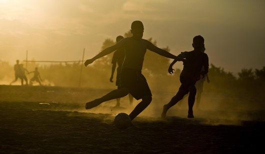 Lao boys kick up dust on the banks of the Mekong in Vientiane, Laos.