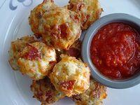 pizza muffinky 1 ¾ hrnku hladké mouky ¾ hrnku mléka ½ hrnku nastrouhaného sýru ¼ hrnku rajčatového protlaku 2 lžičky cukru 1 ½ lžičky prášku do pečiva 1 lžíce oliv 2 stroužky česneku 1 cibule ½ papriky 60g másla 1 vejce 3 plátky slaniny (či jiné uzeniny) oregano nebo bazalka sůl Na másle opražíme cibuli a papriku až změkne, ochladíme a přidáme do moučné směsi,  smícháme. Zvlášť smícháme vejce, mléko, protlak a přidáme do směsi. Formy naplníme, posypeme sýrem a pečeme 20-25 min.180°