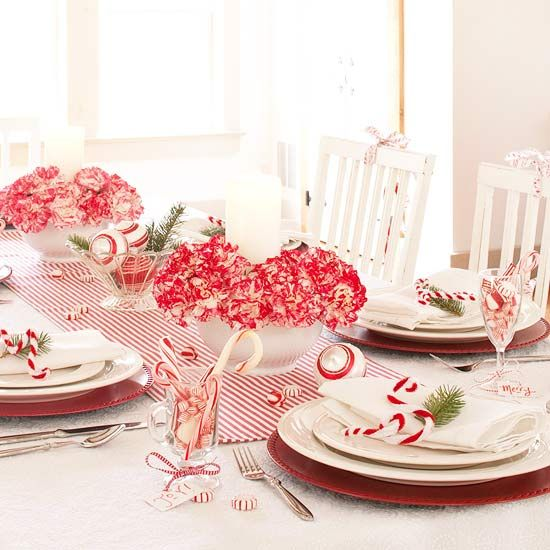Candy Canes and Carnations Holiday Centerpiece:   Add high-contrast punch to white table linens with a few touches of red. Red-and-white carnations and a striped runner (easily made from a fabric remnant) draw the eye to the center of this table and establish the candy cane theme. Fill a pretty glass bowl with