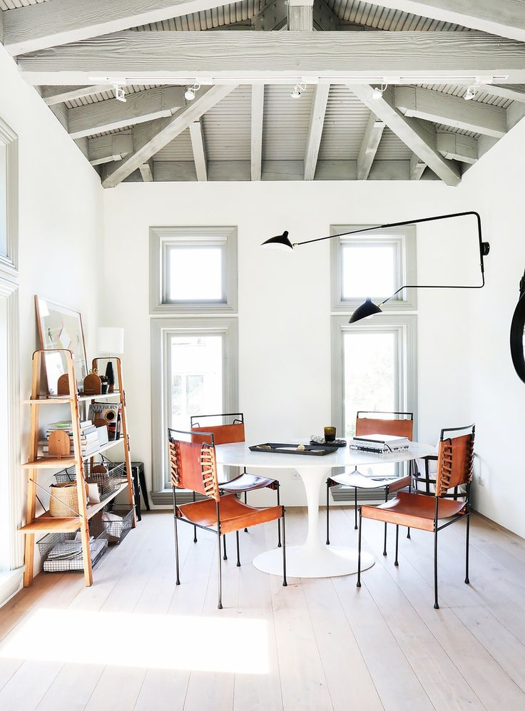 Modern dinning space with vintage brown leather chairs, and a black pendant lamp
