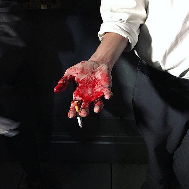 the blood on sh's hand is starting to dry now. sh can smell its faint metallic scent when he brings his hand up to his lips to smoke his cigarette.