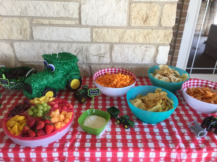 """Farm 2nd Birthday Party snack table - red checkered tablecloth, tractor piñata and toy tractors as table decor. """"Fruit stand"""" platter, """"Potato Patch"""" chips selection, """"Tractor Tires"""" Oreos. Piñata from www.shindigz.com, tablecloth, checkered bowls, wire basket, and chalkboard signs from Hobby Lobby, tractor toys and handkerchief from Tractor Supply, blue bowls from Walmart, and Tupperware divided platter."""