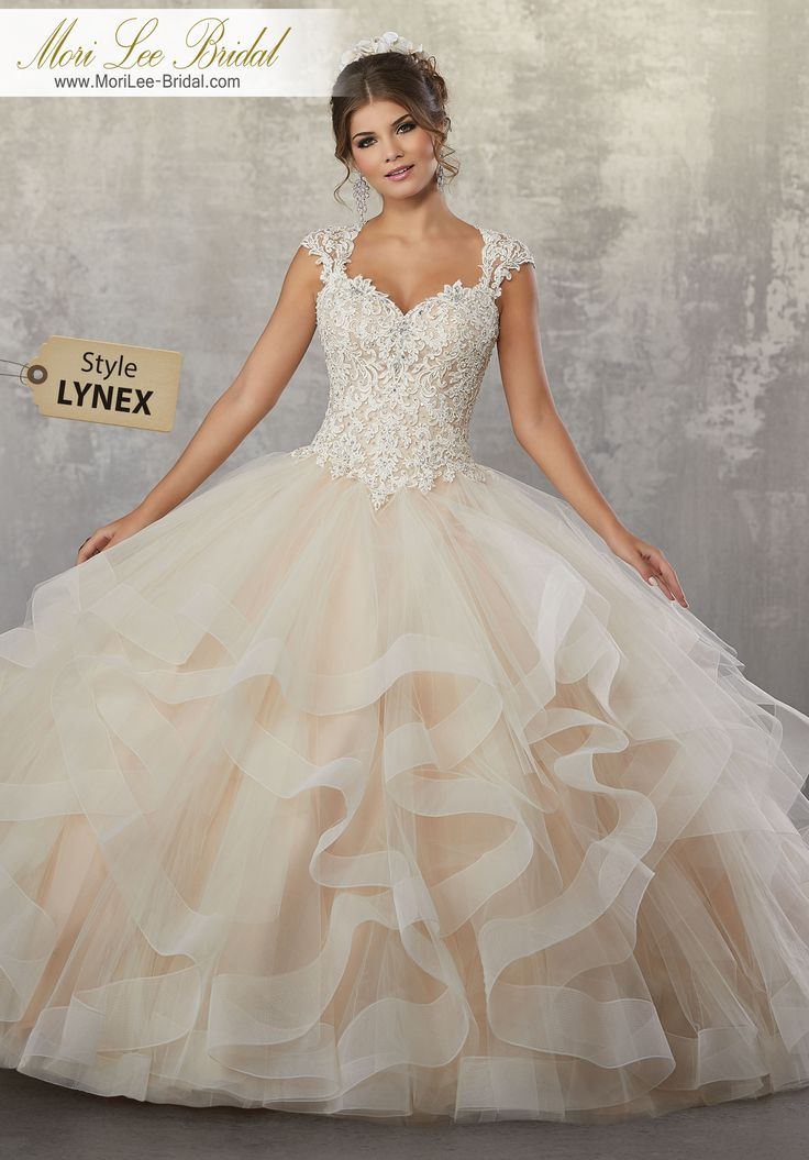 Style LYNEX Beaded, Lace Appliqués on a Flounced Tulle Ballgown with Necklace Back Detail Soft and Sweet, This Gorgeous Quinceañera Ballgown Features a Beaded Lace Bodice Accented with a Delicate Necklace Back. Matching Stole Included. Colors Available: Champagne/Nude, Blush/Champagne, White