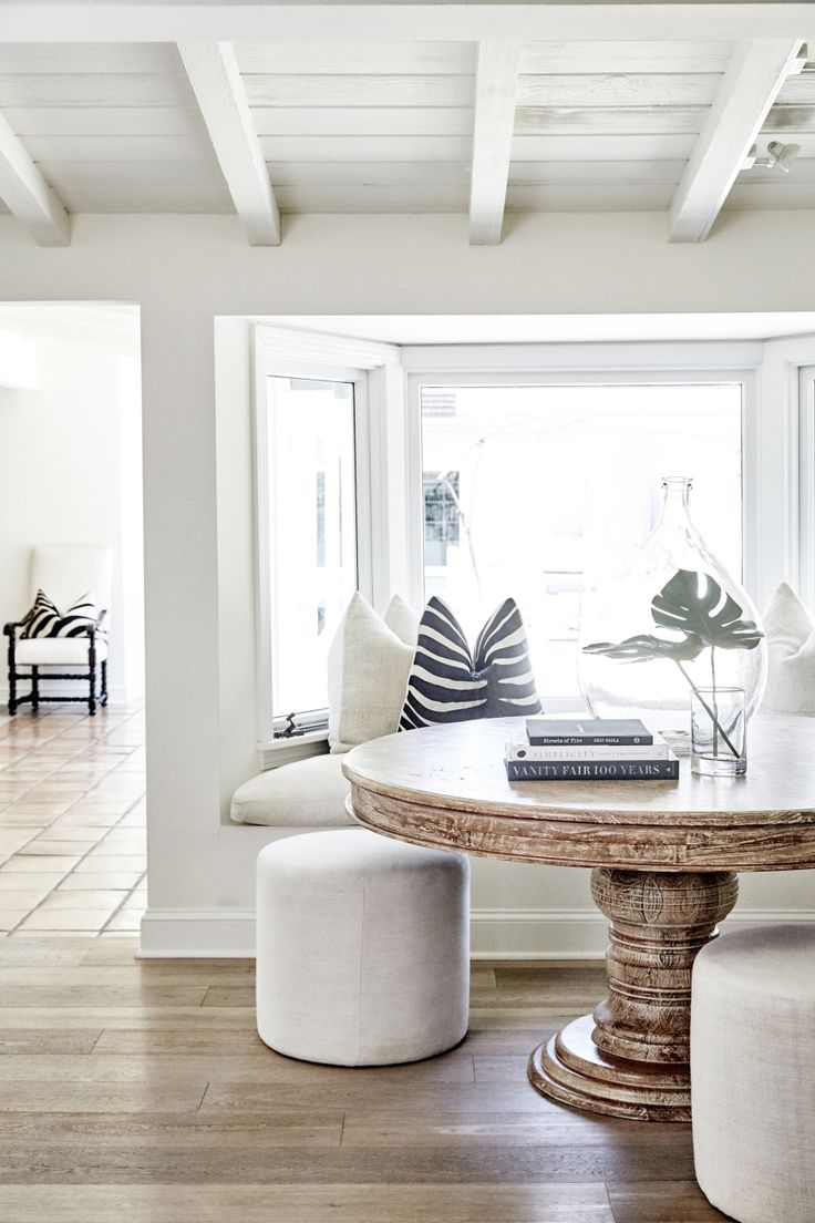 bright white dining room with round table and built in bench seating | Photography: Jenna Peffley
