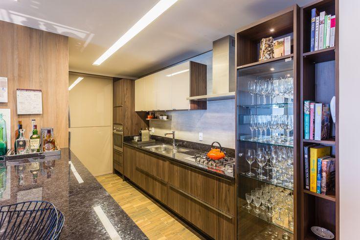 A cozinha foi projetada pra ter personalidade! O uso de Laminato Piastra Scura, Vidro Cristallo Vanilla com puxadores Libero Nuovo Escovado, nos armários, e de pedra natural marrom nas bancadas, criou um ar de sofisticação acompanhando a sala, sem modismos e com total praticidade.