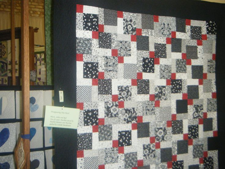 One of a pair of single bed quilts made from Disappearing 9 Patch blocks, in black, white and red.