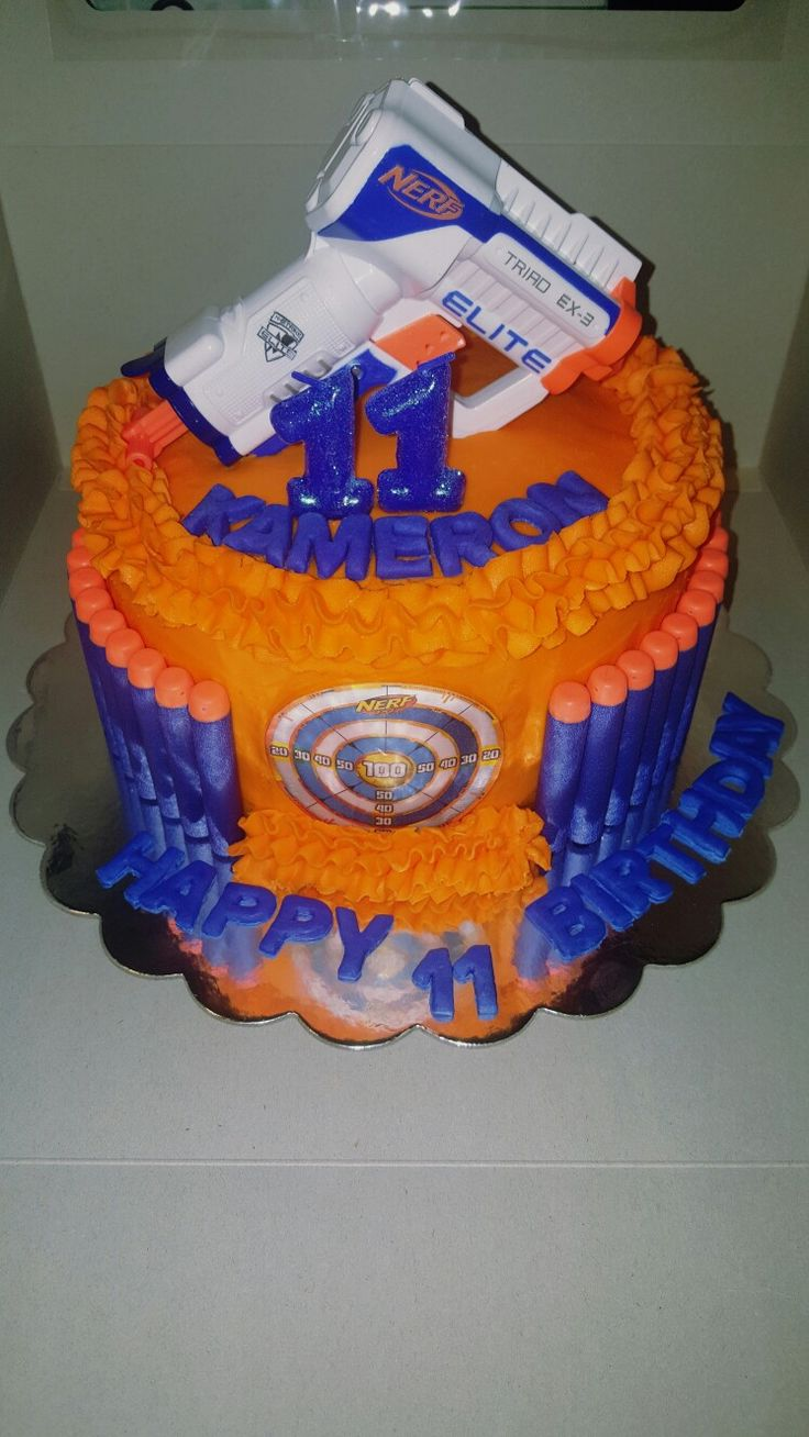 "Nerf Birthday Cake for son's 11th birthday.  8"" 3 layer cake made with buttercream icing and fondant for the letters. Nerf foam bullets going around the side (approximately 1 1/2 packs=45), and a Nerf gun (bought new and washed before placing on cake)."