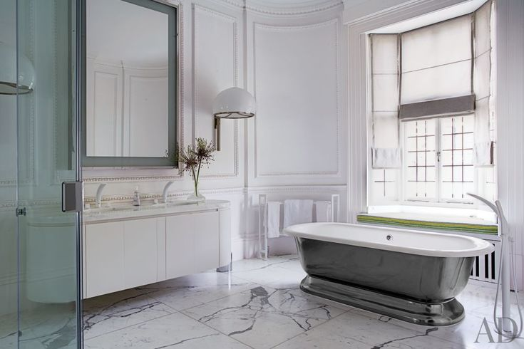 A tub by the Water Monopoly is matched with a Corian vanity in a London home's bath.