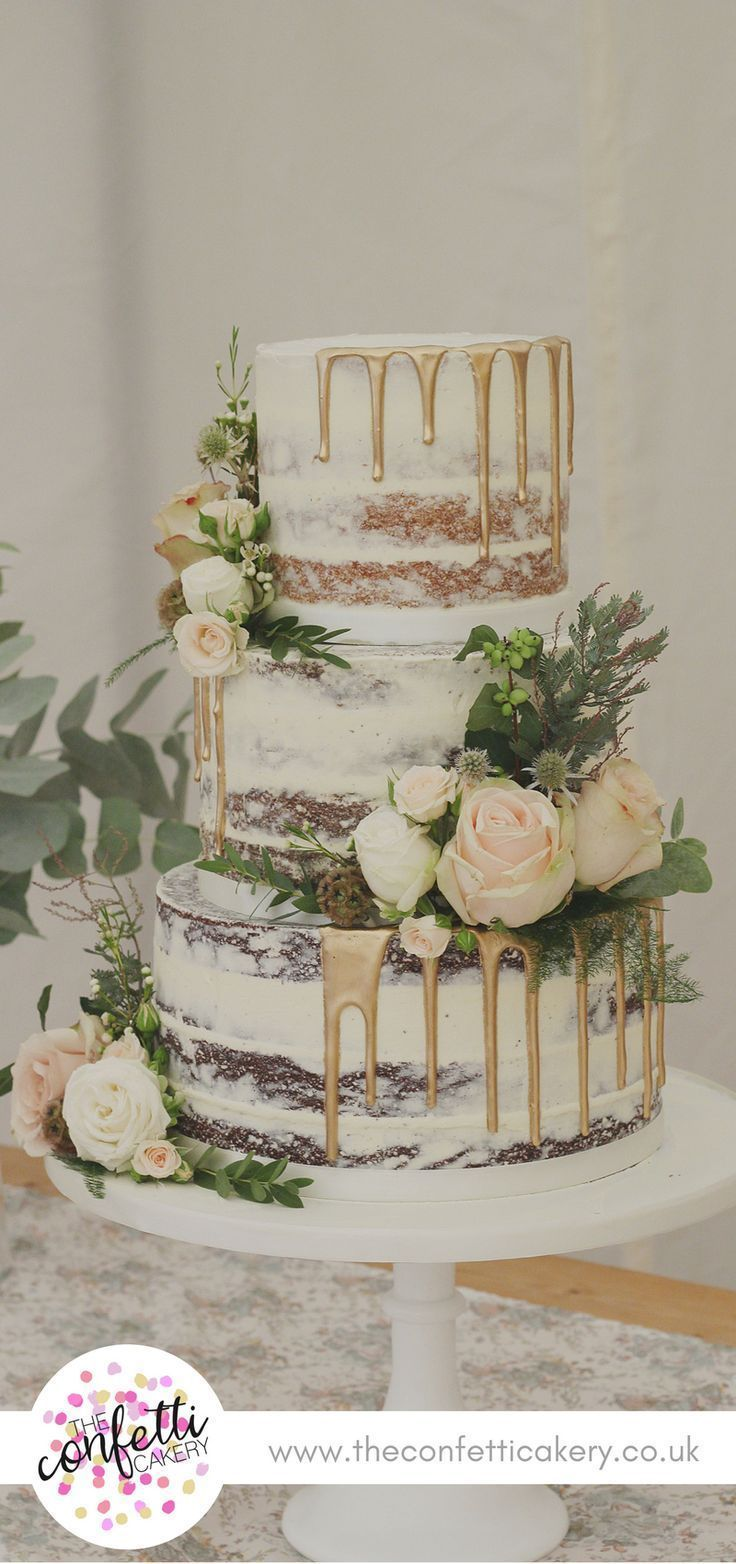Half-naked wedding cake with golden drops and fresh flower and leaf deco…