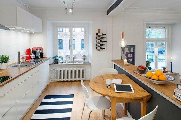 cuisine semi ouverte, placards blancs, petite table en bois, trois chaises