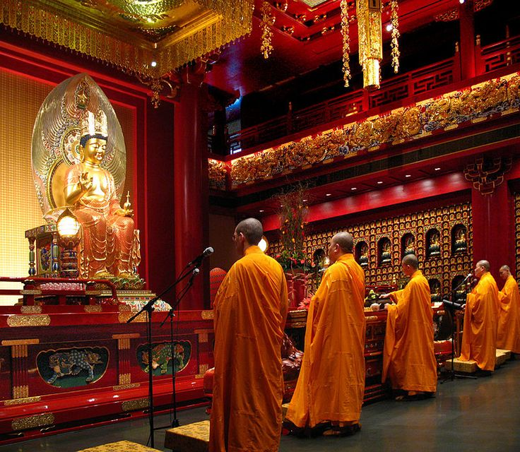 Buddhist adepts pray in the Hundred Dragons Hall, Buddha Tooth Relic Temple and Museum, Singapore, wearing saffron-coloured robes.