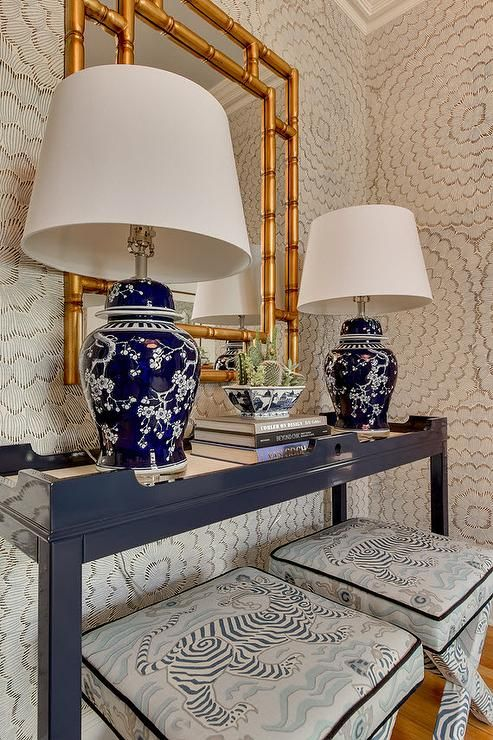Gorgeous foyer features walls clad in Schumacher Celerie Kemble Feather Bloom Wallpaper lined with pair of x stools Clarence House Tibet Print Pale Blue Fabric tucked under a navy console table, Oomph Online Fenwick Console Table, topped with navy lamps, Brohman Table Lamps, as well as gold bamboo mirror, Bassett Sloan Wall Mirror.