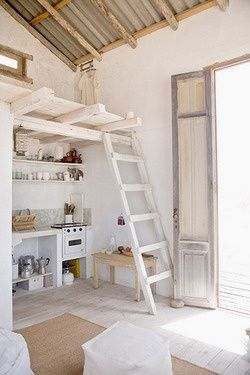 Cottage adorable kitchen. Ladder stairs to loft. Whitewashed wood walls and floors.