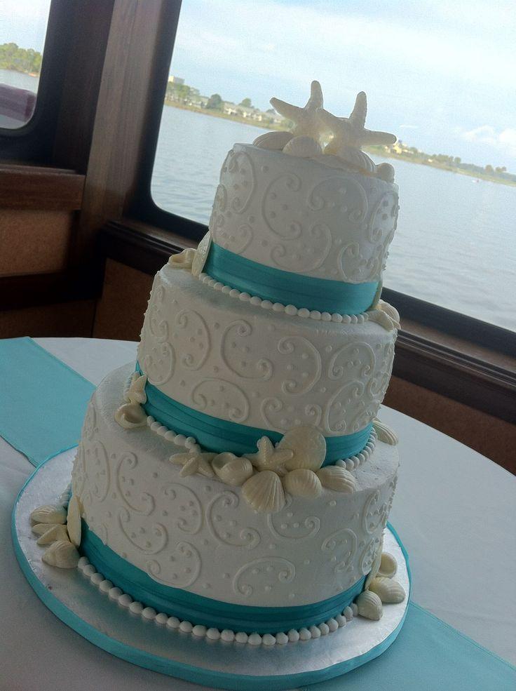 """Jessica"" 3 tier white wedding cake with seashells, swirls, & aqua ribbon border.  Feeds 100.  MSRP $420"