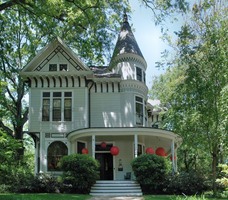 Modest light green Victorian home with large front round porch situated among trees