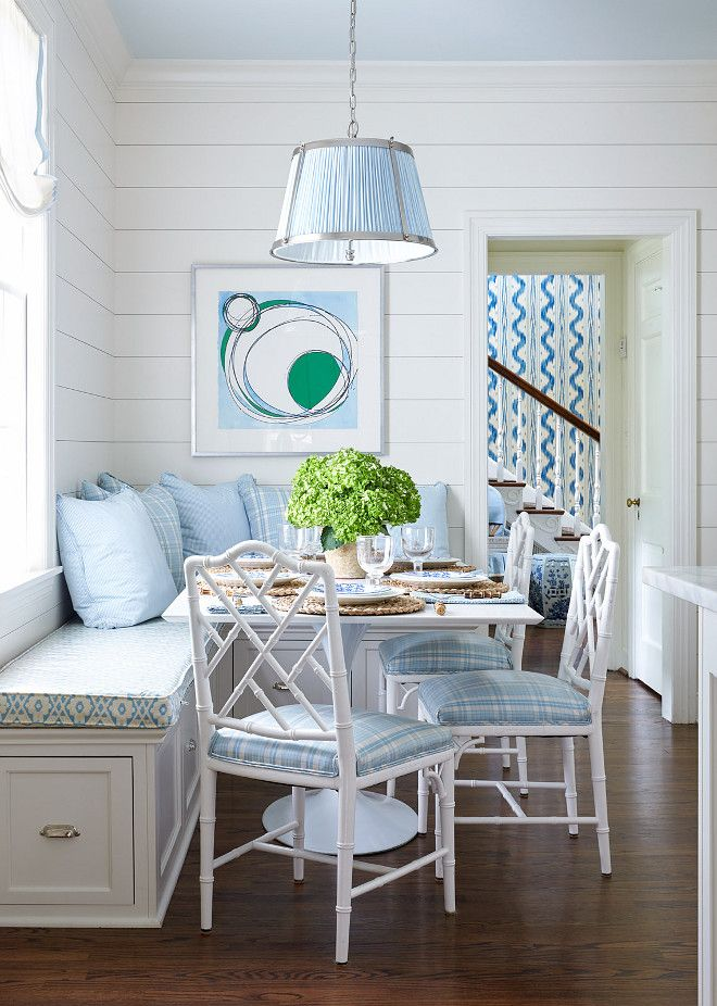 Shiplap White and Blue Breakfast Room with White Bamboo Chairs. Blue and white breakfast room features a blue Vaughn Nickel Hanging Shade Pendant hung from a blue ceiling over a square white dining table seating three white bamboo chairs accented with blue plaid seat cushions complementing blue plaid and solid blue pillows placed atop an L-shaped dining bench adorning polished nickel cup pulls and a blue trellis cushion positioned beneath a window dressed in a white roman shade. The space…