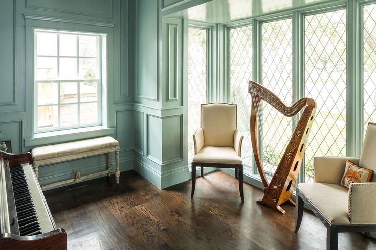 Beautiful interior design and architecture in a music room in a classically designed traditional home by The Fox Group. Harp and piano look sculptural in the timeless, serene space with aqua green millwork. #musicroom #traditionaldesign #harp #paneling