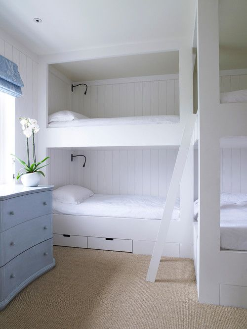 Simple, coastal bedroom with four bunk beds, a jute rug, white bedding and shiplap walls | Thorp Design