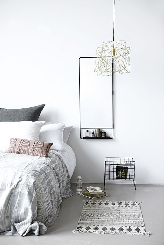 A magazine rack by bedside table to store reading things.  White inspired Scandinavian interior design