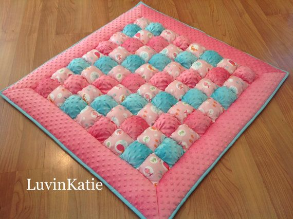 This hot pink and aqua blue bubble puff quilt has a Under the Sea theme. This blanket is ideal for floor time and makes an excellent travel blanket so your little one always has a soft and comfortable place to lay. This quilt is handmade and measures approximately 37 inches by 37 inches. Each of the 64 individually sewn and hand stuffed puffs are made with 100% cotton or minky fabric and stuffed with poly fill. This quilt is incredibly soft. It is bordered with a super soft pink colored…