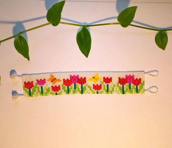 Deze armband moet herinneren aan het late voorjaar met bloeiende kleurrijke tulpen en vlinders frituren boven hen. Het moet u brengen vrolijkheid en alle goede gevoelens wanneer alles begint te bloeien. Het was gemaakt van witte Rocailles als hoofdkleur en rood, roze, oranje en geel voor de bloemen en vlinders.  Lengte: 18 cm of 7,09 inch Breedte: 3 cm of 1,18 inch  Kleur en grootte kunnen worden gewijzigd! Bij het bestellen, gelieve uw omtrek pols kiezen in de vervolgkeuzelijst opties of…