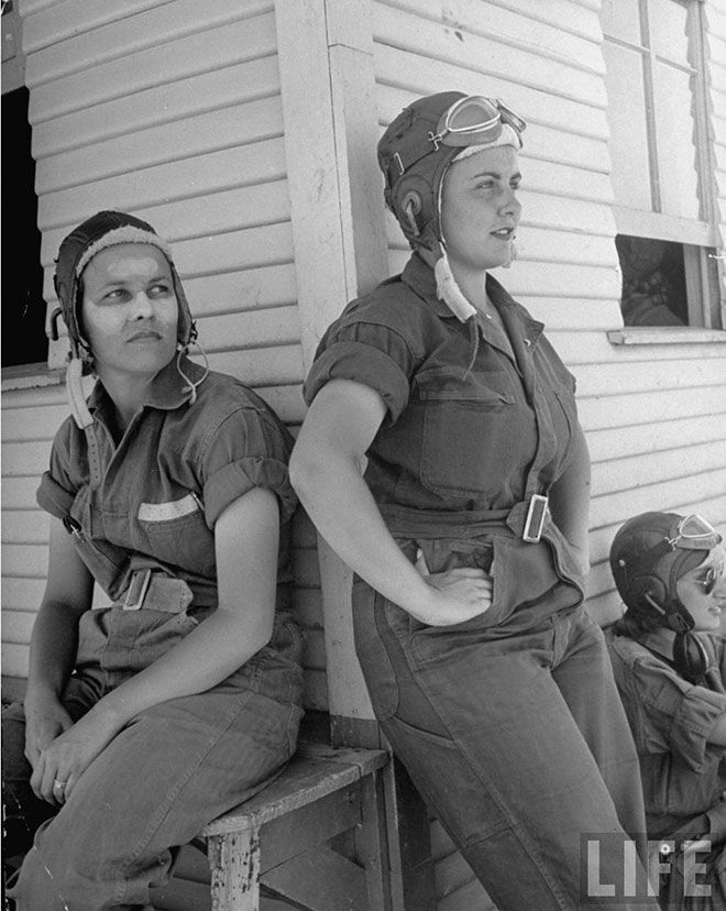 """Girl Pilots"" in WASP training at Avenger Field, Sweetwater Texas, summer 1943: ""Sunburned nose and forehead daubed with cream, Rebecca Edwards of Yazoo City, Miss, is a 22-year-old widow whose husband was killed on duty with the Army Air Forces. Leaning against the corner of the hangar is Lorena Daly of Bakersfield, Cal. They wear the GI coveralls that are regulation for working hours... not very glamourous, but the girls like their comfort and freedom."" Entire original article at link!"
