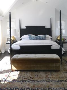 white bedroom with black bed and brown upholstered bench