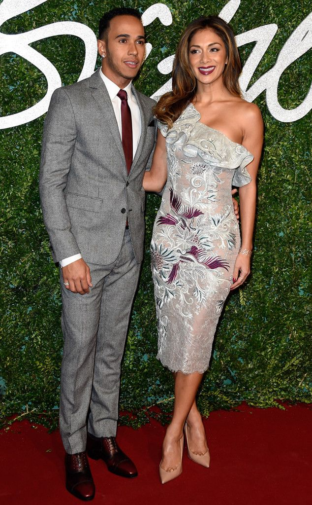 Lewis Hamilton & Nicole Scherzinger from Stars at the 2014 British Fashion Awards  The polished duo work a gray color palette, with Lewis in a soft gray tux and Nicole working a ruffled, one-shoulder design.