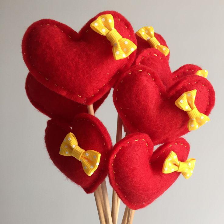 Kit de 8 corações em feltro vermelho com lacinho amarelo e cabo de madeira.    Eles podem ser usados amarrados juntos como um buquê, fincados na grama para casamentos no campo, ou fincados na areia para casamentos na praia! :)    Cada coração tem aproximadamente 8cm de largura por 7cm de altura (...
