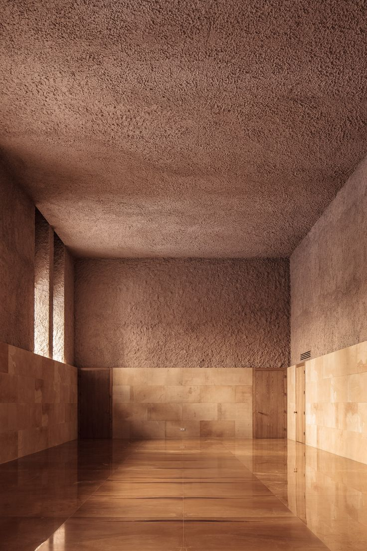 Italian architect Antonino Cardillo has coated the walls of a vaulted chamber-music and events space in lumpy coral-pink, grey and green plasterwork