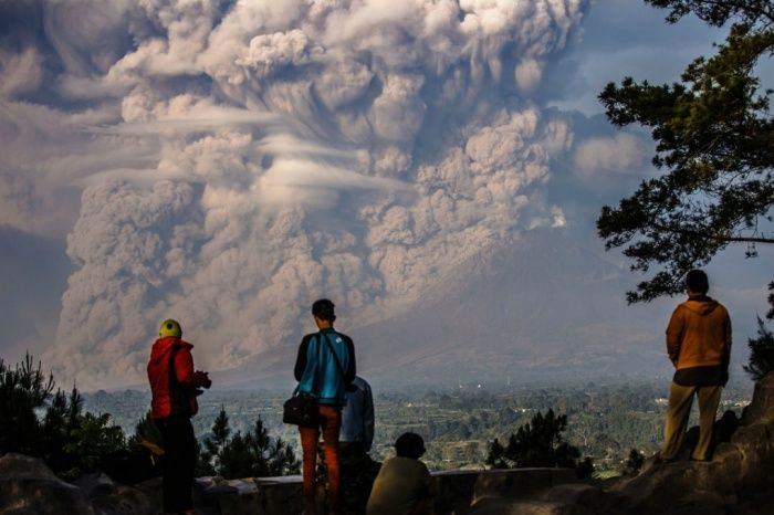 People watch as Mount Sinabung sends ash billowing into the air during an eruption in Karo Indonesia