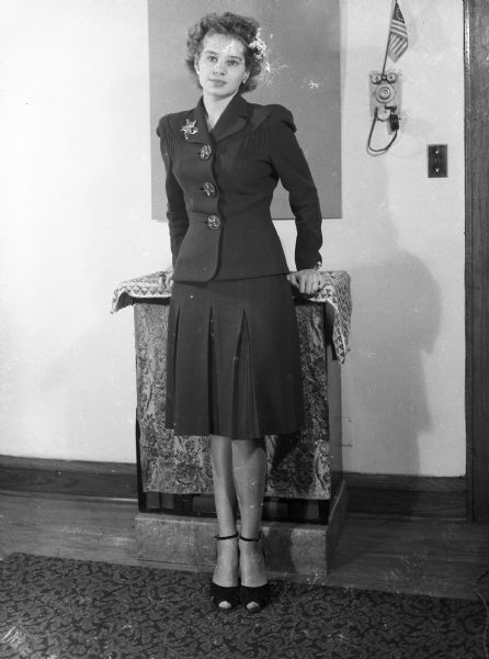 Formal portrait of Angie Vail (nee Siajn), taken by Harold Gauer in his Brady Street apartment. On the wall a small American flag is propped on the apartment intercom. Image ID: 65282