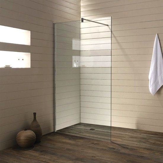 A glass wall panel creates a corner shower; photo via from Cesana.