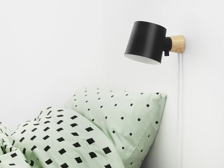 Marianne Andersen designed the uncomplicated Rise wall lamp with only a steel shade and a wooden base for Normann Copenhagen.